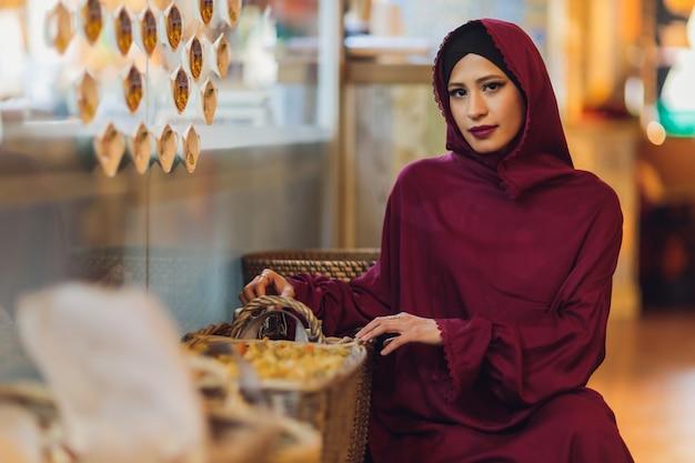 Arabska młoda muzułmanka siedzi w kawiarni