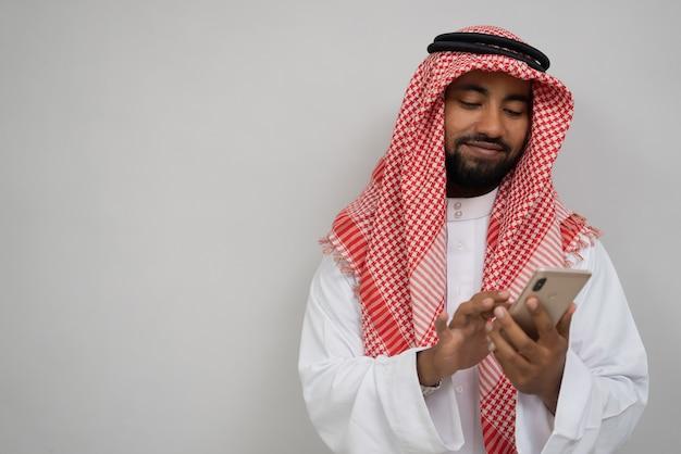 Arabska młodzież w turbanie używająca telefonu komórkowego, który wyciera ekran z uśmiechem