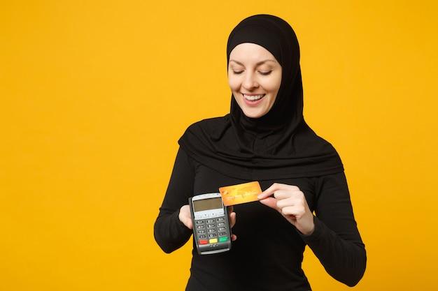 Arabska muzułmanka w czarnych ubraniach hidżab trzyma terminal płatniczy w celu przetwarzania i uzyskiwania płatności kartą kredytową na żółtej ścianie. koncepcja życia religijnego ludzi.