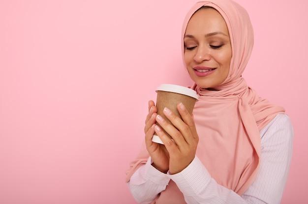 Arabska muzułmańska ładna kobieta z zakrytą głową w różowym hidżabie pijąca gorący napój, herbatę lub kawę z jednorazowego kartonowego kubka na wynos, stojąca trzy czwarte na kolorowym tle z miejscem na kopię