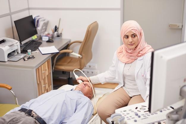Arabska pielęgniarka bada pacjenta seniorów