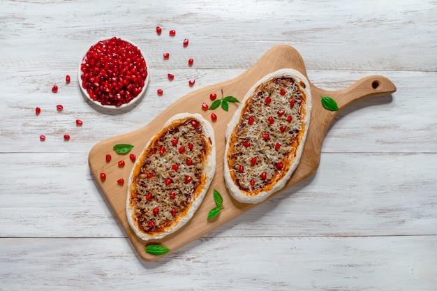 Arabska pizza na drewnianym stojaku. bułeczki z mięsem mielonym i granatem.
