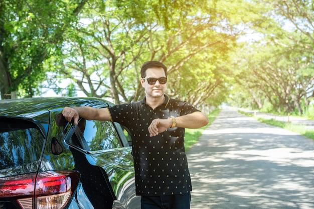 Arabska ręka mężczyzna oprzeć na samochodzie i spojrzeć na oglądać samochód z boku