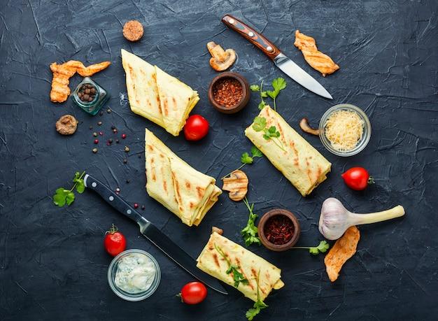 Arabska shawarma z kurczakiem, serem i grzybami. fast food