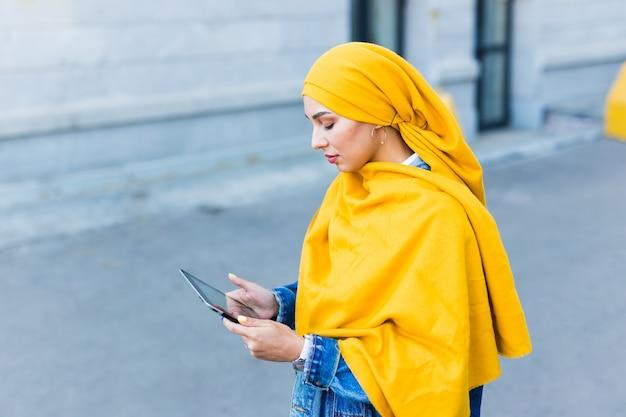 Arabska studentka. piękna muzułmańska studentka ubrana w jasny żółty hidżab trzymając tabletkę, przestrzeń miejska