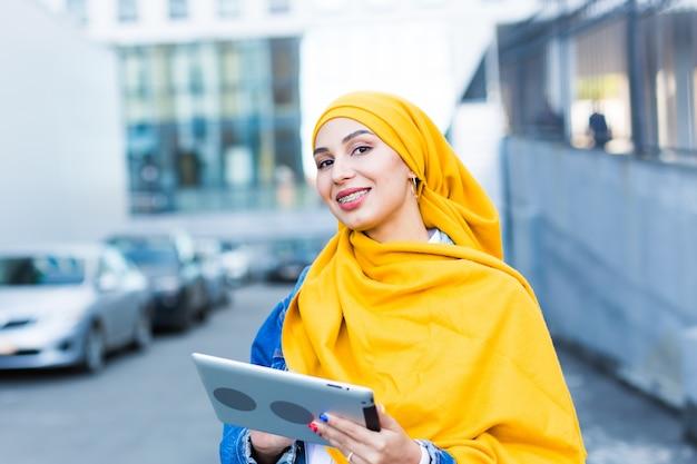 Arabska studentka. piękna muzułmańska studentka ubrana w jasny żółty hidżab trzymając tabletkę.