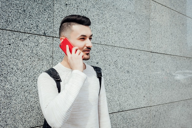 Arabska studentka z plecakiem dzwoniąca do przyjaciół na zewnątrz