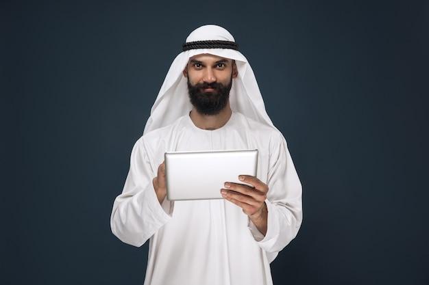 Arabski biznesmen saudyjski na ciemnym niebieskim tle studio