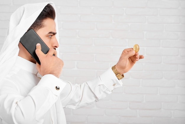Arabski biznesmen w tradycyjnych strojach wygląda na złotym bitcoinie