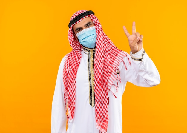 Arabski biznesmen w tradycyjnym stroju i masce ochronnej na twarz z pewnym wyrazem twarzy przedstawiającym znak zwycięstwa stojący nad pomarańczową ścianą