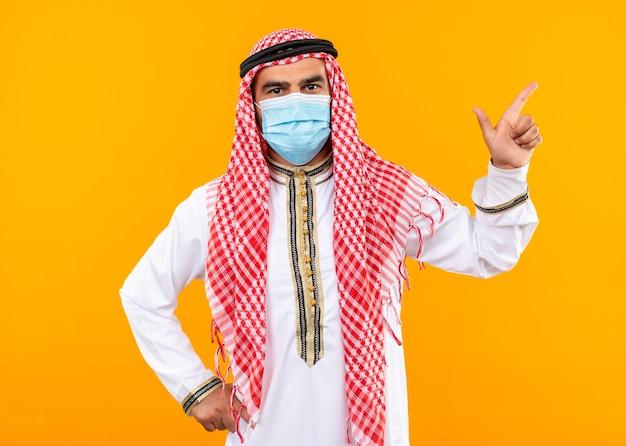 Arabski biznesmen w tradycyjnym stroju i masce ochronnej na twarz z pewnym wyrazem twarzy wskazującym w bok z palcem wskazującym stojącym nad pomarańczową ścianą