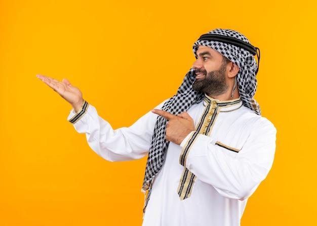 Arabski biznesmen w tradycyjnym stroju, patrząc w bok, wskazując palcem i ramieniem na bok, stojąc na pomarańczowej ścianie