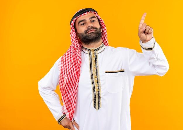 Arabski biznesmen w tradycyjnym stroju, pewny siebie, wskazując palcem w bok, stojąc nad pomarańczową ścianą