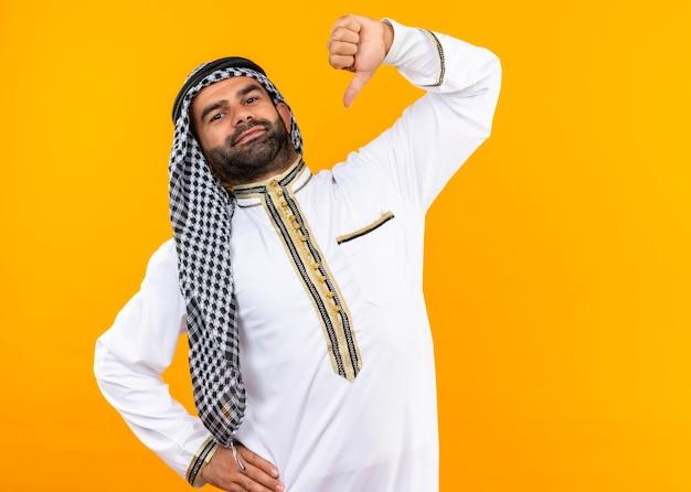 Arabski biznesmen w tradycyjnym stroju, wskazując na siebie zadowolony z siebie, dumny stojąc nad pomarańczową ścianą
