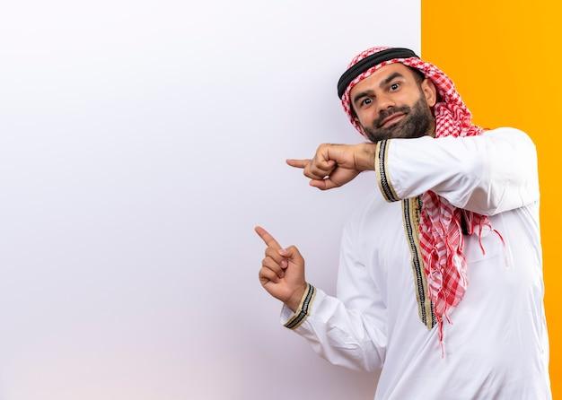 Arabski biznesmen w tradycyjnym zużyciu stojący w pobliżu pustej tablicy, wskazując palcami na nią z pewnym uśmiechem na twarzy na pomarańczowej ścianie