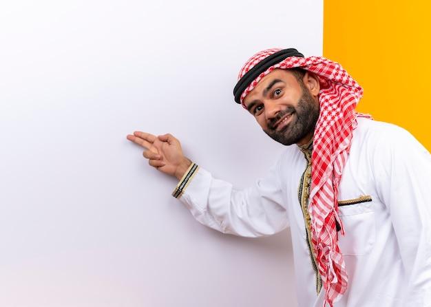 Arabski biznesmen w tradycyjnym zużyciu stojący w pobliżu pustej tablicy, wskazując palcami na nią z uśmiechem na twarzy na pomarańczowej ścianie