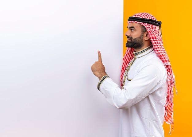 Arabski biznesmen w tradycyjnym zużyciu z białą pustą tablicę wskazującą palcem w górę uśmiechnięty stojący nad pomarańczową ścianą