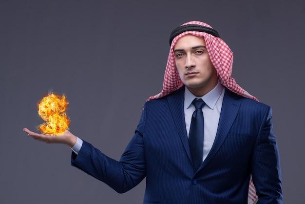 Arabski biznesmen z płonącym dolarowym znakiem