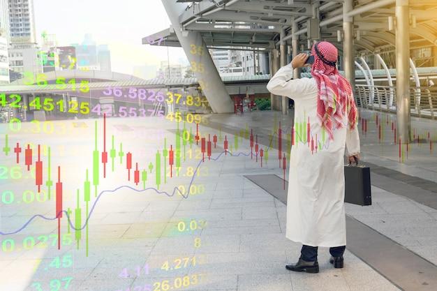 Arabski biznesmena czeka wykres na smartphone, finansowy pojęcie