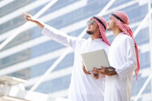 Arabski biznesowy mienie laptop pracuje w mieście
