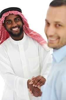 Arabski i europejski amerykański biznesowy mężczyzna robi transakci i handshaking