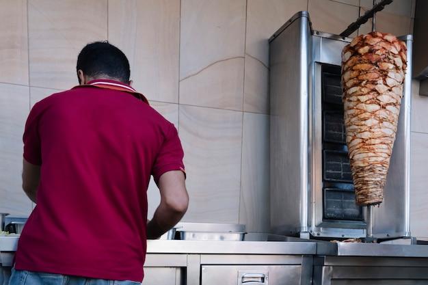 Arabski kucharz przygotowuje shawarmę, kroi mięso. stojąc tyłem do aparatu, na rożnie smaży się wołowinę lub kurczaka mayaso
