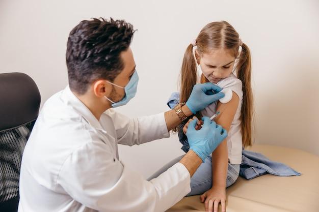 Arabski lub turecki lekarz podaje małej dziewczynce szczepionkę na koronawirusa. dziewczyna się boi. wysokiej jakości zdjęcie