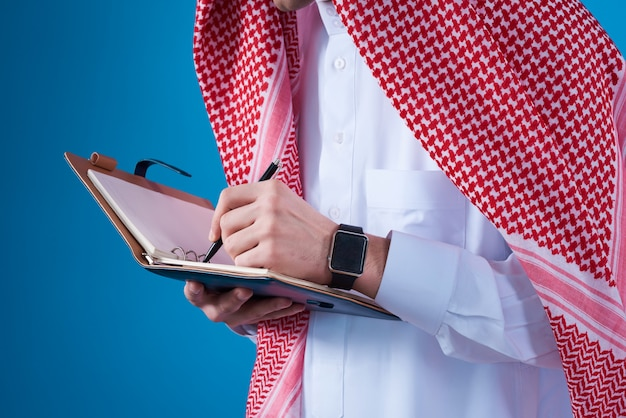 Arabski mężczyzna bierze notatki w notatniku odizolowywającym.
