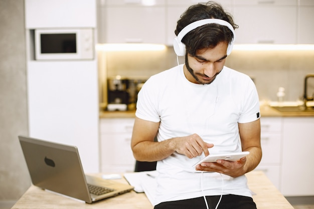 Arabski mężczyzna ogląda webinarium online, siedzi w kuchni z komputerem i cieszy się nauką na odległość