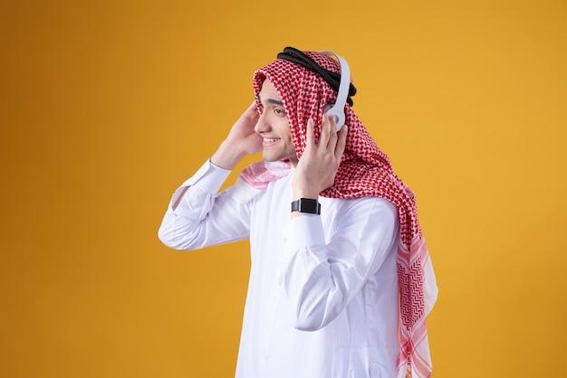 Arabski mężczyzna pozuje słuchać muzyka odizolowywająca.