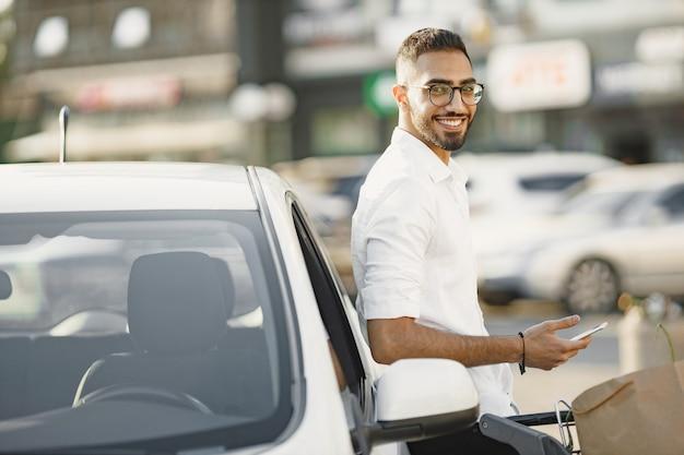 Arabski mężczyzna używa inteligentnego telefonu, czekając na ładowanie baterii w samochodzie. świadomość ekologiczna.