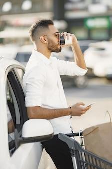 Arabski mężczyzna używa inteligentnego telefonu, czekając na ładowanie baterii w samochodzie.