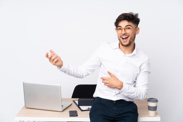 Arabski mężczyzna w biurze na białej ścianie robi gitara gestowi
