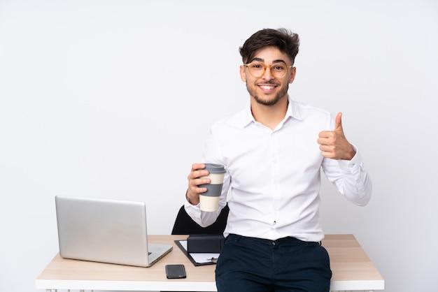 Arabski mężczyzna w biurze na biel ścianie pokazuje ok znaka i kciuka up gestykuluje