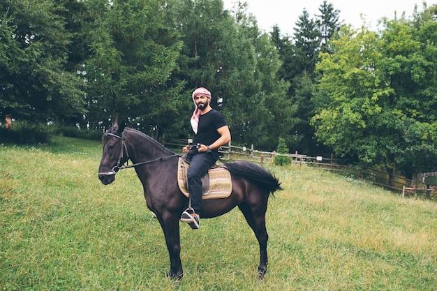 Arabski mężczyzna w czarnych ubraniach siedzi na koniu