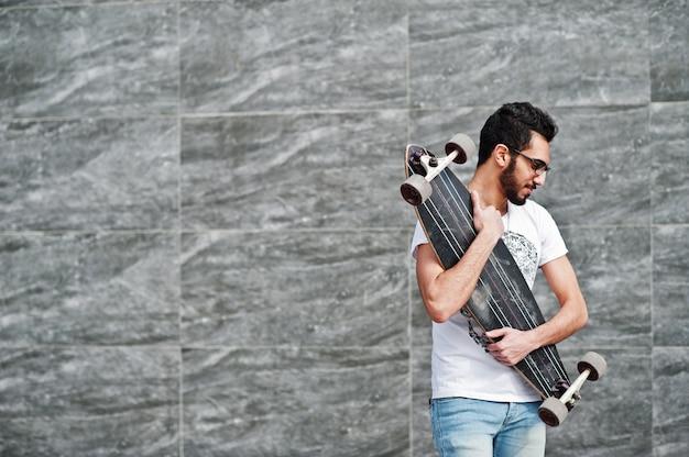 Arabski mężczyzna w stylu ulicy w okularach z longboard postawionych na szarej ścianie.