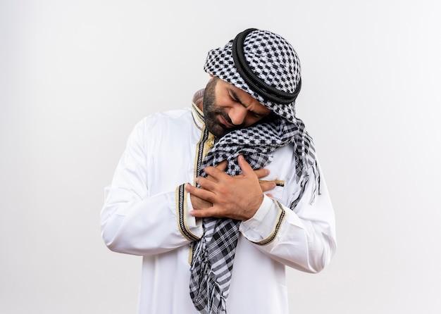 Arabski mężczyzna w tradycyjnym stroju, trzymający się za ręce na klatce piersiowej, patrząc niechętnie na ból stojącego nad białą ścianą