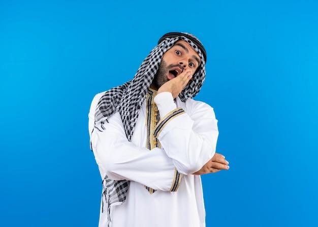 Arabski mężczyzna w tradycyjnym stroju zaskoczony i zdumiony stojąc nad niebieską ścianą