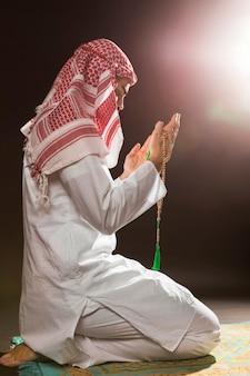 Arabski mężczyzna z kandora modli się i trzyma koraliki modlitewne