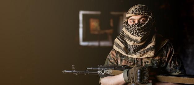 Arabski mężczyzna żołnierz w nakryciu głowy z narodowego kefija z bronią w ręku