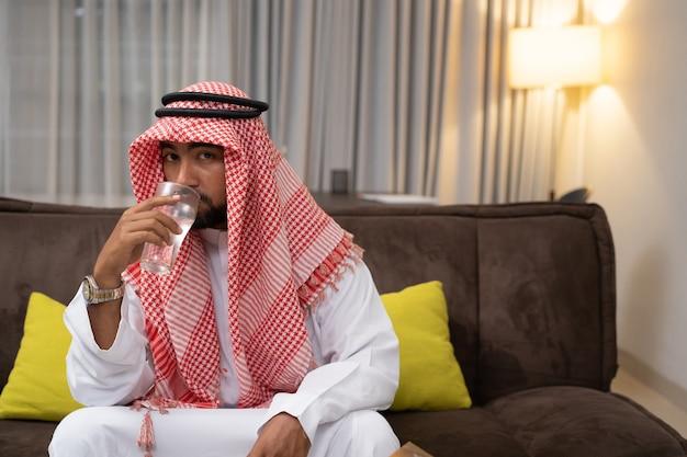 Arabski młody człowiek pijący wodę za pomocą szklanki