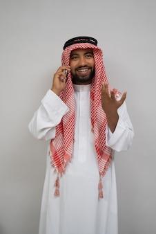 Arabski młody mężczyzna w turbanie dzwoni przez telefon komórkowy, uśmiechając się gestem ręki