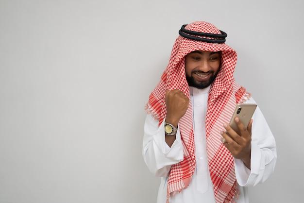 Arabski młody mężczyzna w turbanie korzystający z telefonu komórkowego radośnie patrzący na ekran z podekscytowanym ...