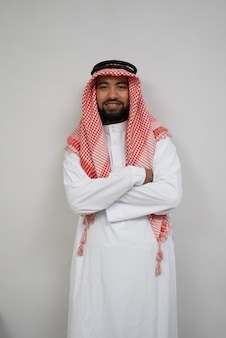 Arabski młody mężczyzna w turbanie stojący uśmiechnięty ze skrzyżowanymi rękami