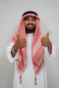 Arabski młody mężczyzna w turbanie, uśmiechnięty, stojąc, patrząc w kamerę z kciukami do góry, podczas gdy...