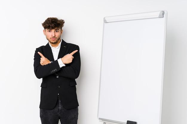 Arabski młody trener biznesowy wskazuje bokiem, próbuje wybrać jedną z dwóch opcji.