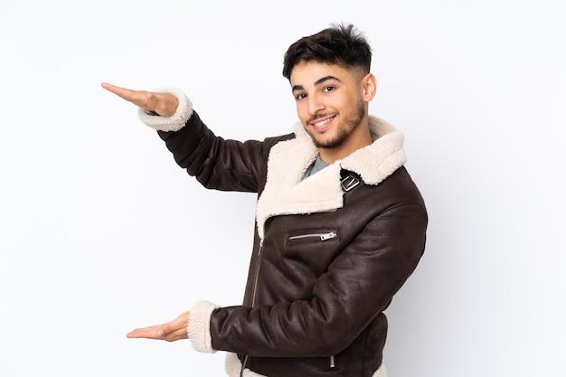 Arabski przystojny mężczyzna na białym tle gospodarstwa copyspace, aby wstawić reklamę