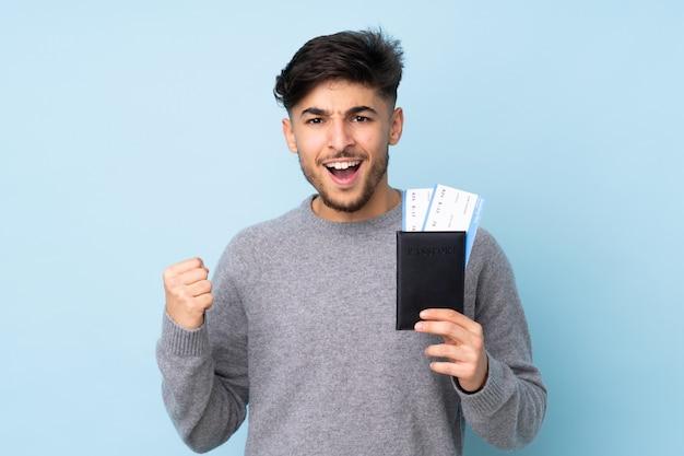 Arabski przystojny mężczyzna na białym tle na niebieskiej ścianie szczęśliwy na wakacjach z biletami paszportowymi i lotniczymi