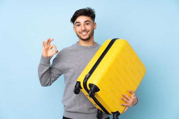 Arabski przystojny mężczyzna na białym tle na niebieskiej ścianie w wakacje z walizką podróżną i robi znak ok