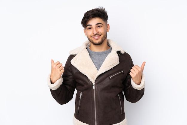 Arabski przystojny mężczyzna na białym tle z kciuki do góry gest i uśmiechnięty